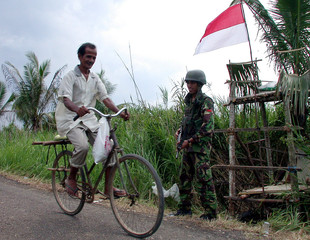 ACEHNESE MAN RIDES A BICYCLE PAST AN INDONESIAN SOLDIER AT COT TRIENGVILLAGE IN NORTH ACEH.