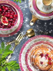 Fresh juicy berry cranberry, pancakes, tea, green leaves on a dark blue background flat view
