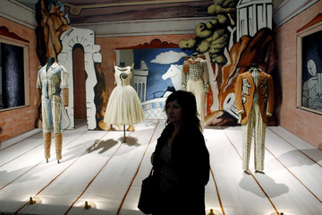 "A woman walks past a Surrealist ballet set on the opening day of ""Surreal Things"", a 250-piece art exhibition at the Guggenheim Museum in Bilbao"