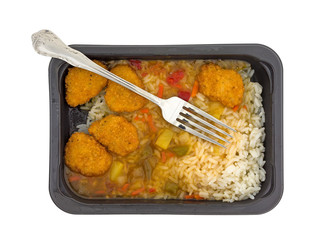 Sweet and sour chicken TV dinner with a fork in the food isolated on a white background top view.