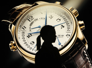 A woman is silhouetted as walks past the Longines showcase at the eve of the opening of the Baselworld in Basel
