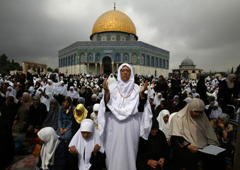 Palestinian women pray outside Dome of the Rock in Jerusalem