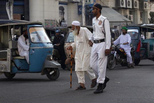 A traffic policeman helps an elderly man cross an intersection in Karachi