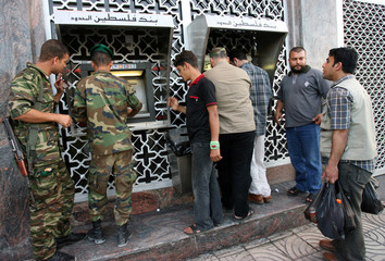 Palestinian government employees and policemen withdraw money in Gaza City