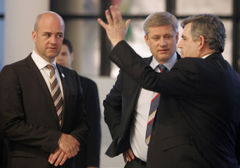 Sweden's PM Reinfeldt speaks with Canada's PM Harper and British PM Brown during the G8 summit in L'Aquila