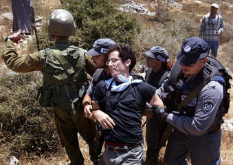 ISRAELI POLICEMEN ARREST AN ISRAELI PEACE ACTIVIST DURING A PROTEST IN THE WEST BANK.