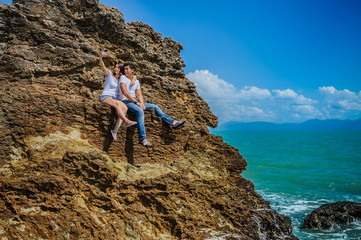 A mixed race couple - Thai man and European woman - at a cliff, watching waves making splashes