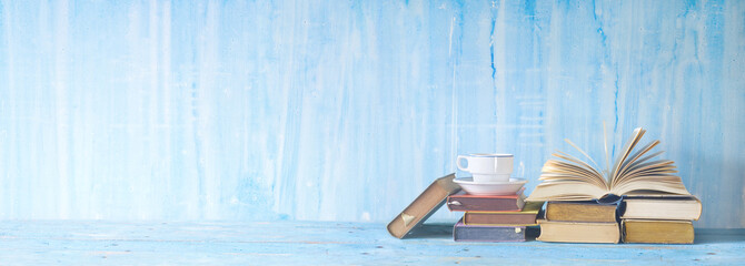 opened book, cup of coffee on blue grungy background, panoramic, copy space