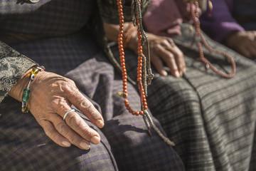 Hands of old buddhist devotee holding prayer beads