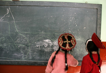 Andean girls in traditional Inca clothes draw a llama in school in the village of Huilloc in Cuzco