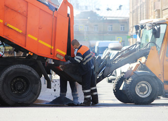 The dump truck pours asphalt crumb into the excavator bucket during extreme road repairs while the cars are moving.