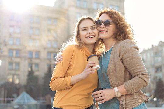 Cheerful mother and daughter having fun in city