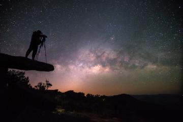 Cameraman takes photo of milky way on Stone lodge under night sky stars