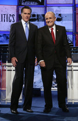 Republican presidential candidates Romney and Giuliani talk on stage before the start of the presidential debate in St. Petersburg