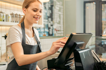 Cheerful shop assistant using digital device for payment