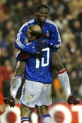 France's Louis Saha (L) celebrates with team-mate Zinedine Zidane (R) after scoring against Belgium ..