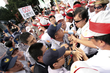 Far Eastern Air Transport employees scuffle with the police during a rally in front of the presidential office in Taipei to urge President Ma to help them