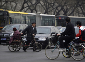 A man pushes a tricycle carrying his wife in front of buses and cars sitting in a traffic jam on a congested main road near Beijing's Tiananmen Square