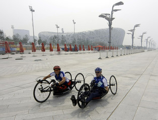 Paralympic cyclist from France trains with her coach for Beijing 2008 Paralympic Games outside National Stadium in Beijing