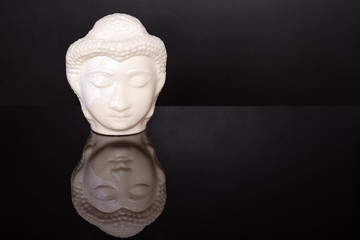 Buddha face. Buddha statue made of white marble on black background with reflection. Concept of peace, calm and tranquility. Buddhist artifact for Zen style interior decor.