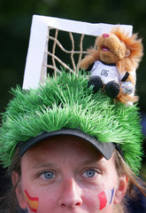 A soccer fan wearing a hat designed with a soccer pitch and a goal walks in Hanover