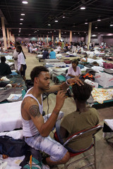 Henry Rhodies, who was evacuated from New Orleans, gives a haircut to a friend in Reliant Arena, ...