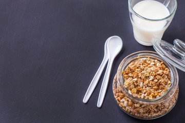 Granola with milk on a black wooden background