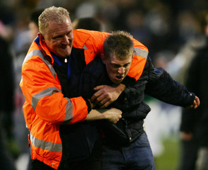 Steward restrains football fan after Fulham beat Chelsea in soccer match at Craven Cottage