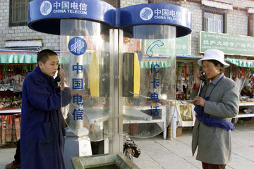 TIBETAN RESIDENTS USE PUBLIC PHONES IN LHASA.