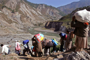 Kashmiris carry food and clothing back to their mountain village in the Neelum Valley north of Muzaffarabad