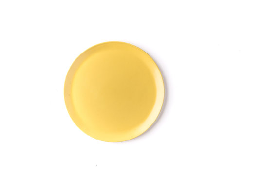 Close up of a round yellow plate on a  white background