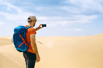 A tourist with a backpack takes photo of the desert by phone