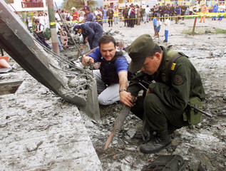 COLOMBIAN INVESTIGATOR CHECK THE REMAINS OF CAR AFTER GUERRILLA CAR BOMB ATTACK.