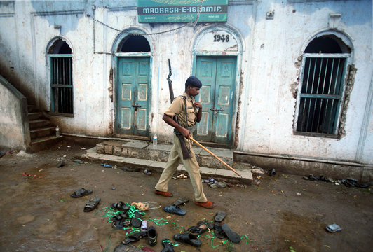A policeman walks past a clutter of torn slippers of blast victims inside a mosque in Malegaon