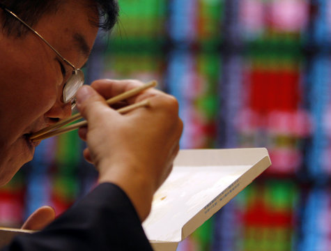 A man eats in front of computer monitors showing stock market prices at a securities company in Taipei