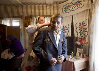 A social worker helps World War Two veteran Murashko to put on his suit in village of Pogost