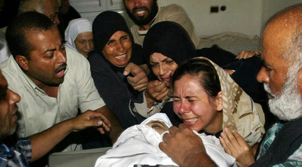 Palestinian relatives of Azah Hamad mourn during her funeral in Rafah