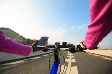 cyclist hands use smartphone cycling on high way