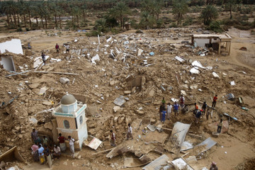 Residents gather at the site of collapsed houses in the oil-rich Sah district in southeastern Yemen