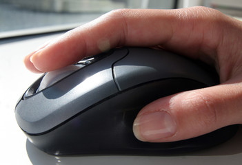 A generic picture of a woman in an office using a computer mouse.