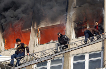 People climb down a rescue ladder to escape from a burning building in Vladivostok