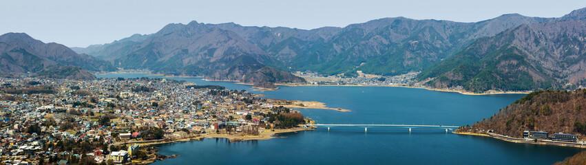 Wide panorama of the town of Fujikawaguchiko and Lake Kawaguchi at the foothills of Mount Fuji in Japan