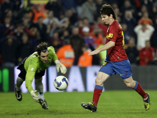 Barcelona's Lionel Messi (R) scores against Benidorm goalkeeper Caballero during their Spanish King's Cup soccer match at the Nou Camp stadium in Barcelona