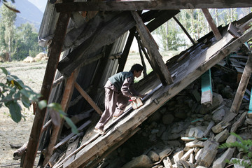 BEST QUALITY AVAILABLE A Kashmiri quake survivor tries to salvage parts of his destroyed home in Kandi