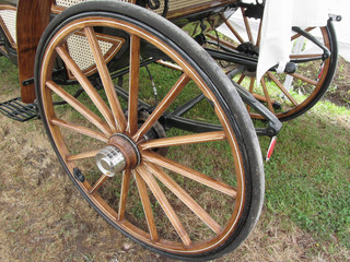 Rear wheels of old-fashioned horse carriage on green grass