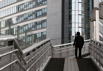 Man walks on a footbridge in Tokyo's Shiodome business district