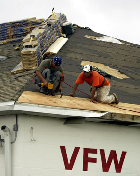 Roofers make repairs to roof damaged by Charley and Frances, as Hurricane Jeanne approaches.