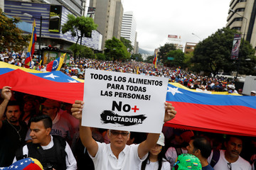 Demonstrators hold Venezuelan flags and a sign reads: ' All the food for all the people! No more dictatorship ' while rallying against Venezuela's President Nicolas Maduro in Caracas
