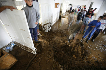 Volunteers remove mud from a mosque which was flooded in the coastal town of Dellys