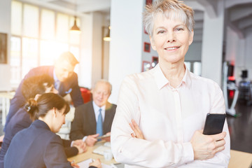 Ältere Seniorin als Geschäftsfrau vor Team